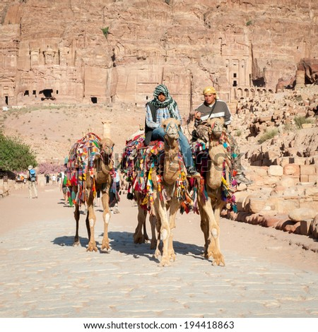 PETRA, JORDAN - APR 29, 2014: Unidentified people ride camels in Petra. The city of Petra was lost for over 1000 years. Now one of the Seven Wonders of the Word