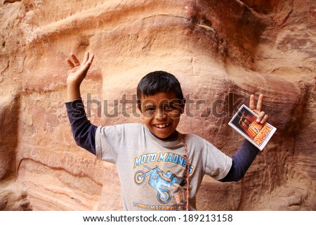 PETRA, JORDAN: APRIL 20, 2014, an unidentified Bedouin boy is happily selling postcards at the tourist attraction site Petra in Jordan - stock photo