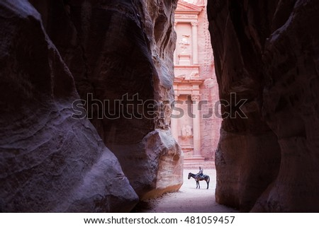 PETRA, JORDAN-AUGUST 16TH, 2016: Unientified man ride a horse in front of the Treasury. Horse camel and donkey are commonly used for transport inside the archeological site, used mostly for tourists.