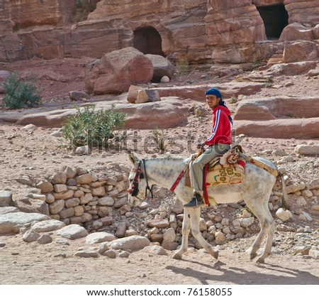 PETRA, JORDAN - NOV 24: Unidentified Bedouin rides his  donkey past the magnificent ruins of ancient Petra on November 24, 2010 in Petra, Jordan. Petra is a UNESCO World Heritage Site since 1985.