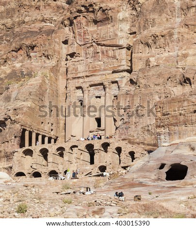 PETRA, JORDAN - OCTOBER 28, 2014: Unidentified tourists near Urn Tomb one of the best preserved tombs hewn into the sandstone cliff. - stock photo