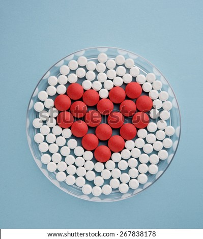 Petri dish with pills forming heart symbol - stock photo