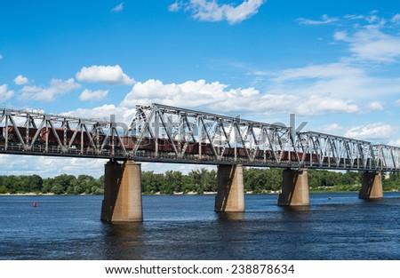 Petrivskiy railroad bridge in Kyiv across the Dnieper with freight train on it. - stock photo