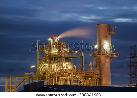 Petrochemical industrial plant with smoking in twilight sky