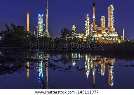Petrochemical plant at night with reflection on water