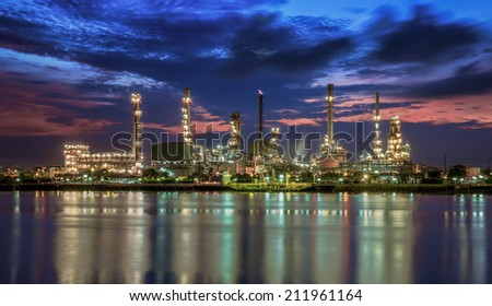 petrochemical plant in night time with reflection over the river - stock photo