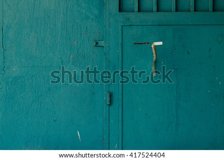 petrol blue wall and door with paper strip - stock photo