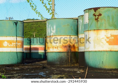 petrol garbage in rusty tank discard form factory long time ago.black oil leak and drop to ground - stock photo