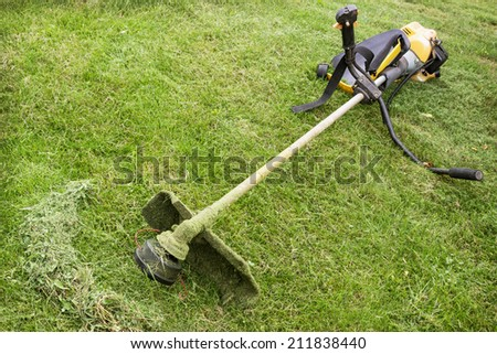 Petrol trimmer is on the sloped lawn in the garden - stock photo