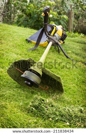 Petrol trimmer on the sloped lawn in the garden - stock photo