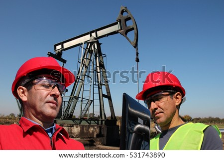 Petroleum Engineers Looking at Laptop Computer / Petroleum engineers next to pump jack in the oil field working with laptop