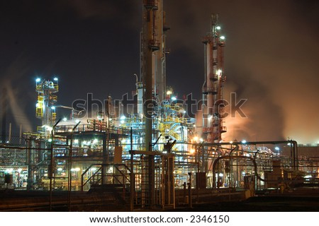 Petroleum refinery by night with billowing clouds of orange smoke - stock photo