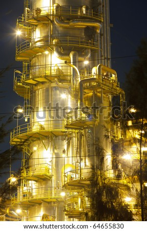 Petroleum refinery distiller column at night - stock photo