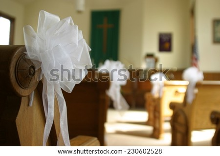 Pews decorated for wedding ceremony white ribbon and bows - stock photo