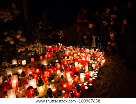 PEZINOK, SLOVAKIA - NOVEMBER 1: People placing candle among candles on ground on All Saints' day on November 1, 2013.