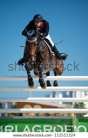 PEZINOK, SLOVAKIA - SEPTEMBER 9: Marko Pandza on horse Contesa jumps over hurdle on Grand Prix Postova Banka-Peugeot on September 9, 2012 in Pezinok, Slovakia - stock photo