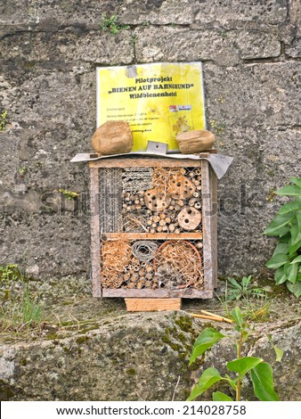 """PFAFFSTAETTEN, AUSTRIA - 31 AUGUST 2014: An insect hotel was set up on a rail tunnel. The sign states, that it is part of the pilot project """"Bienen auf Bahngrund/ Bees on railroad sites"""". - stock photo"""