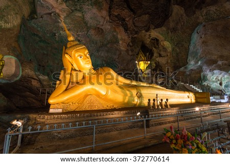 Phang Nga, Thailand - September, 8th, 2015: Golden statue of Reclining Buddha in buddhist cave temple in Wat Tham Suwankhuha cave (Monkey Cave) In Phang Nga, Thailand. - stock photo