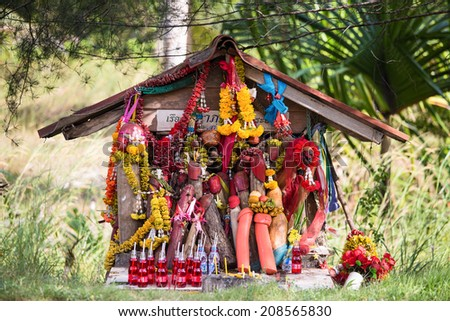 PHANGAN, THAILAND - DECEMBER 24, 2013:View of a Thai spirit house with wooden penises on a city street in Koh Phangan, Thailand. Spirit houses are erected outside businesses and homes to bring fortune - stock photo