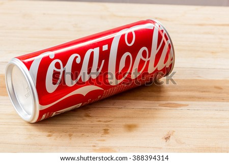 PHARE, THAILAND - MARCH 3, 2016. Coca Cola can on wooden table. Coca Cola drinks are produced and manufactured by The Coca-Cola Company, an American multinational beverage corporation.