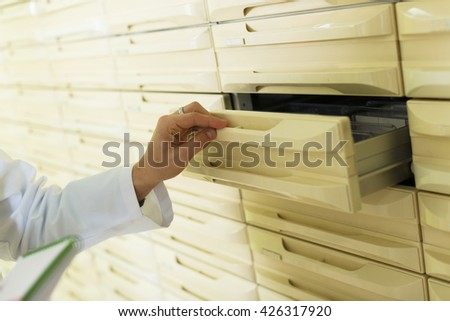 Pharmaceutical chemist opening drawer for drugs  storage  in farmacy - stock photo