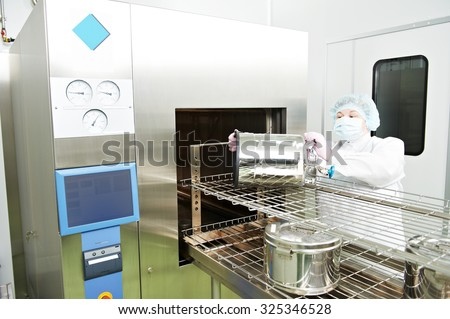 pharmaceutical factory woman worker operating autoclave for medicine drug steam sterilization at pharmacy industry manufacture factory - stock photo