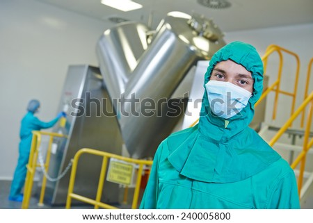 pharmaceutical factory workers in front of powder mixer machine during tablet production at pharmacy industry manufacture factory - stock photo