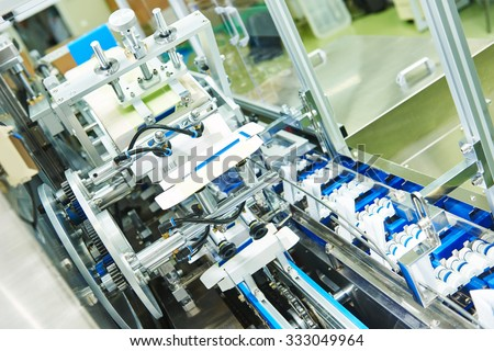 pharmaceutical industry. Line machine conveyer for packaging glass bottles ampoules in boxes at pharmacy factory - stock photo