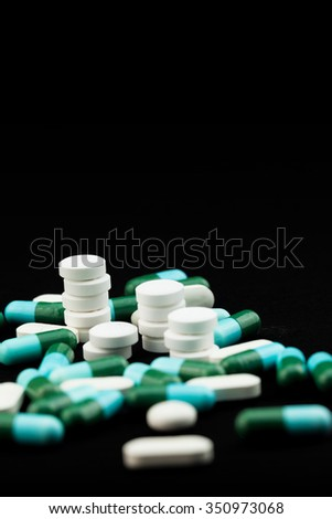 Pharmaceutical medicament, cure in container for health. Antibiotic, painkiller closeup. Medicine pills or capsules over black color background.