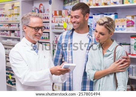 Pharmacist and costumers smiling at pharmacy - stock photo