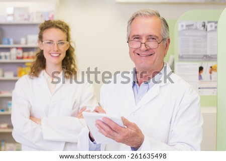 Pharmacist and his colleague with arms crossed behind at pharmacy