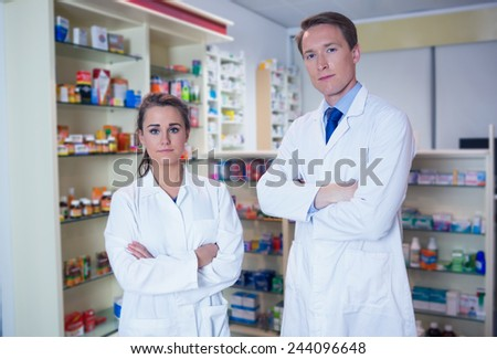 Pharmacist and his trainee standing with arms crossed in the pharmacy - stock photo