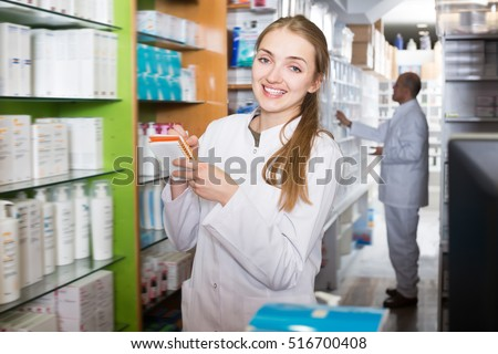 Pharmacist and male assistant helping in drugstore