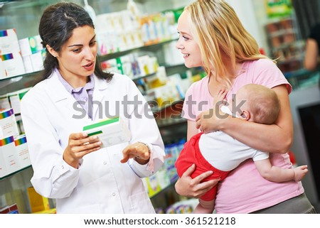 pharmacist chemist woman giving vitamins to mother with child in pharmacy drugstore - stock photo