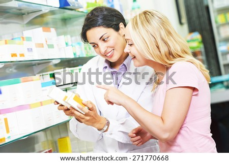 pharmacist chemist woman helps to choose medicine for young to female buyer in pharmacy drugstore - stock photo
