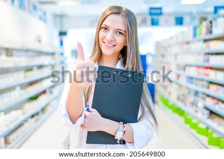 pharmacist chemist woman standing in pharmacy drugstore, smiling - stock photo