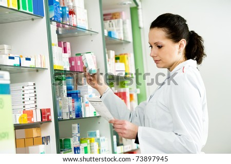 pharmacist chemist woman working in pharmacy drugstore - stock photo