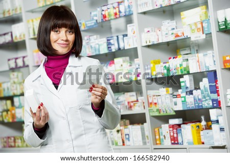 pharmacist chemist woman working in pharmacy drugstore with doctor prescription - stock photo