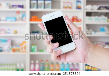 pharmacist hand holding smart phone in the pharmacy - stock photo