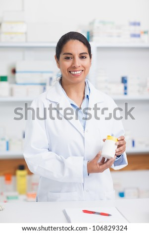 Pharmacist holding a drug box in hospital - stock photo