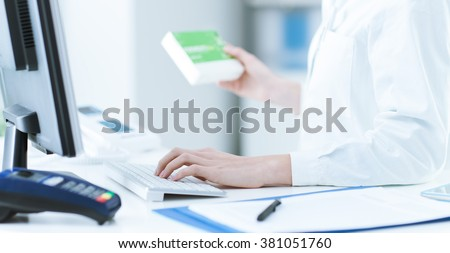 Pharmacist holding a medicine packet and searching that product in the computer database, healthcare and technology concept