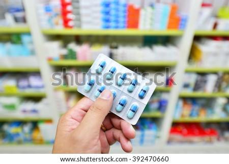 Pharmacist holding medicine capsule pack at the pharmacy drugstore - stock photo