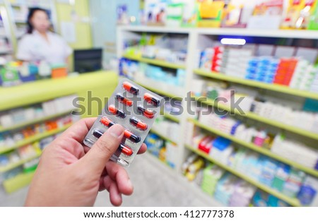 Pharmacist holding medicine capsule pack at the pharmacy drugstore - stock photo