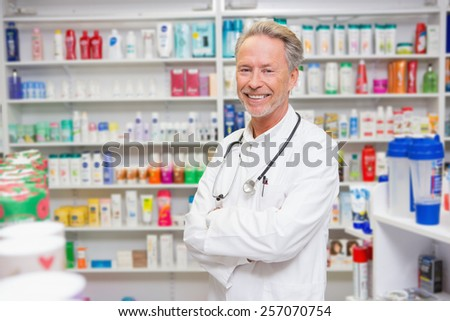 Pharmacist in lab coat with stethoscope and arms crossed in the pharmacy - stock photo