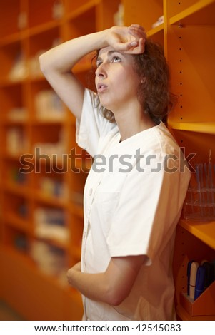Pharmacist leaning at shelf and taking a rest