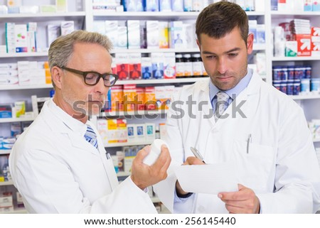 Pharmacist looking a medication for a prescription in the pharmacy - stock photo