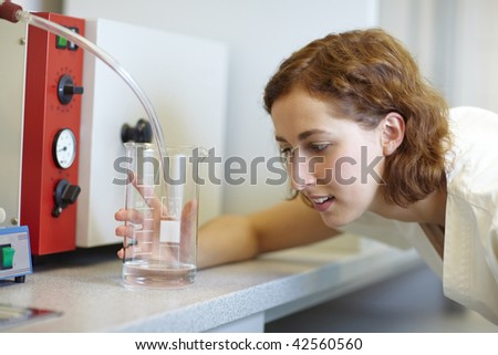 Pharmacist looking at measuring cup in laboratory
