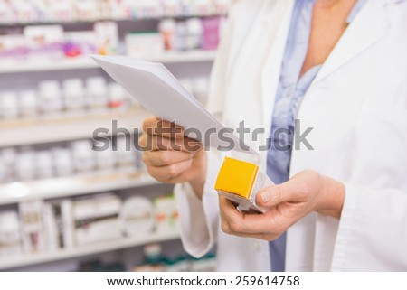 Pharmacist looking at prescription and medicine in the pharmacy - stock photo