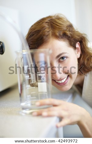 Pharmacist looking through measuring cup in laboratory