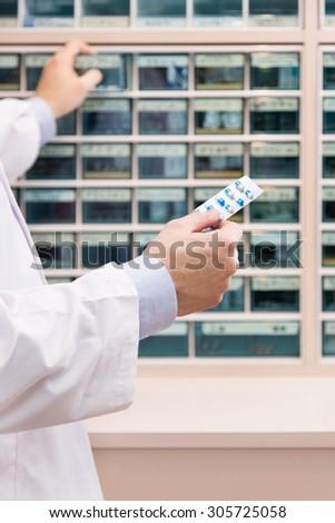 Pharmacist man choosing medicines at pharmacy. Drug store.Medical image.  - stock photo